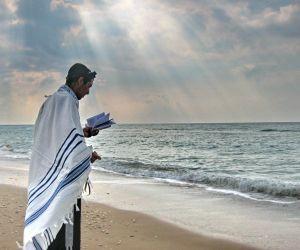 A Man in Tel Aviv prays on the beach